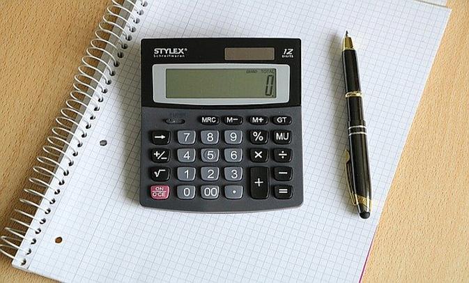 Taschenrechner und Stift auf kariertem Block